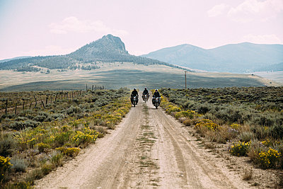 Friends riding motorbikes on dirt road against sky - p1166m1521771 by Cavan Images