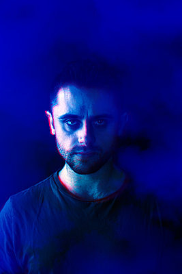 Man staring at camera against blue background - p1248m2287872 by miguel sobreira
