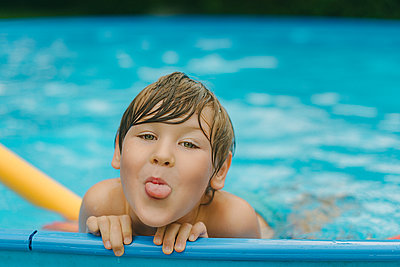 Boy in pool, portrait - p1400m2161071 by Bastian Fischer