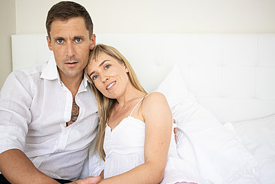 Happy couple sitting on bed, portrait - p1640m2259622 by Holly & John