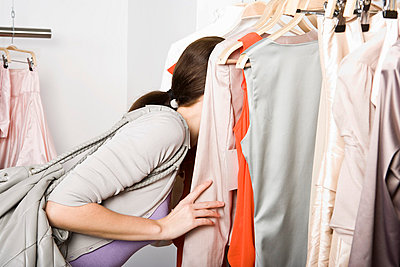 A woman searching through a clothes rail in a store - p3018898f by Paul Hudson