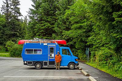 Man and camper van on parking lot, Tofino, British Columbia, Canada - p343m2047022 by Ben Girardi