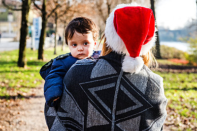 Over shoulder view of young woman in santa hat carrying baby boy in park - p429m1227217 by Bonfanti Diego