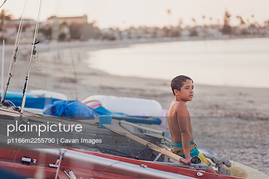 Young boy sitting on a docked boat at the beach. - p1166m2255790 by Cavan Images