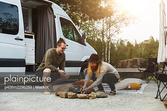 Male friends preparing campfire by motor home - p426m2296259 by Maskot