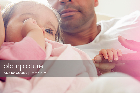 Baby girl sucking thumb with comfort blanket on father's lap - p429m1418466 by Emma Kim