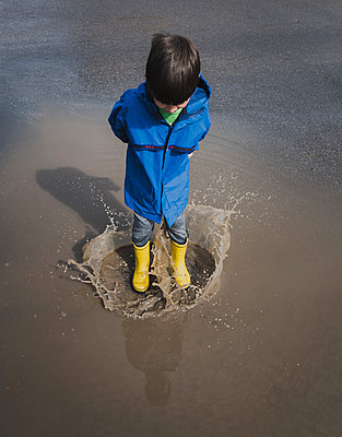 High angle view of playful boy wearing rubber boots while jumping in puddle - p1166m2011822 by Cavan Images