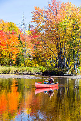 A man canoes through shallow water in a Maine river. Fall. - p1166m2094349 by Cavan Images