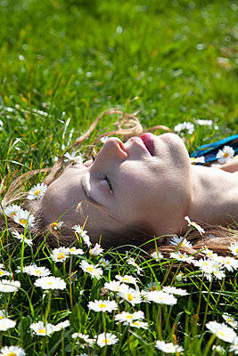 Woman Lying on Grass with Daisies  - p1248m2087692 by miguel sobreira