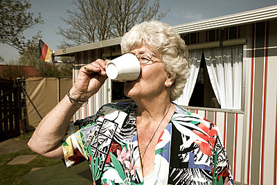 Elderly woman drinking coffee on a camping site - p2610630 by Jens Rufenach