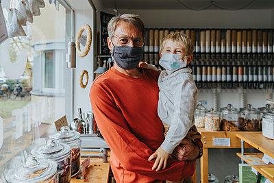 Father and son standing in zero waste shop, Cologne, NRW, Germany - p300m2256252 von Mareen Fischinger