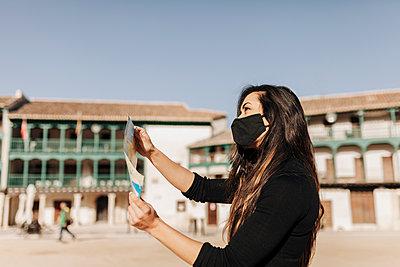 Tourist wearing protective face mask checking map - p300m2282611 by Manu Reyes