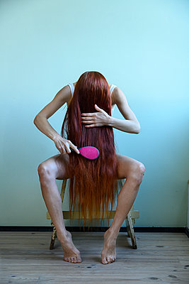 Red-haired woman combing her hair - p427m2211216 by Ralf Mohr