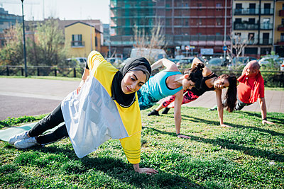 Calisthenics class at outdoor gym, women and man practicing sideways yoga position - p429m2098282 by Eugenio Marongiu