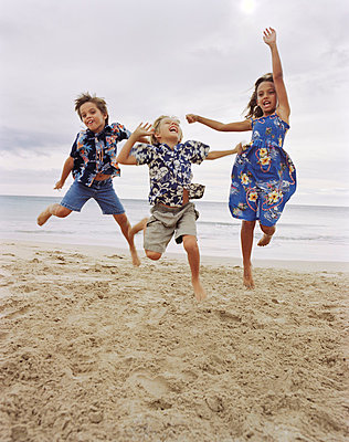 Children jumping together on beach - p429m768067 by David Jakle