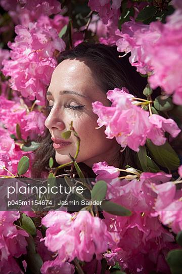 Frau genießt Rhododendren-Blüten - p045m1154674 von Jasmin Sander