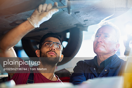 Male mechanics working under car in auto repair shop - p1023m2196744 by Tom Merton