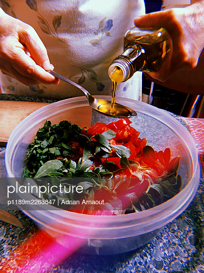 Putting olive oil in a salad - p1189m2263847 by Adnan Arnaout