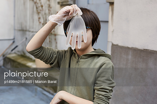 Boy playing with plastic gloves during Covid-19 quarantine - p1499m2181585 by Marion Barat