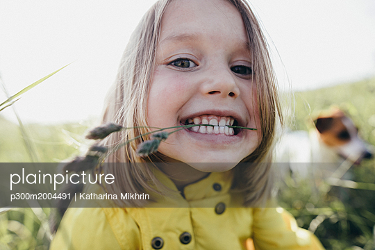Portrait of little girl on a meadow holding blade of grass with her teeth - p300m2004491 von Katharina Mikhrin