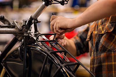 Midsection of man fixing nut of bicycle - p1166m1096012f by Cavan Images