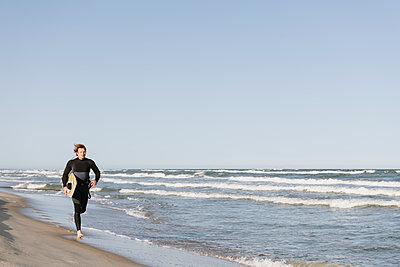 Surfer running at the beach - p300m2118693 by Hernandez and Sorokina