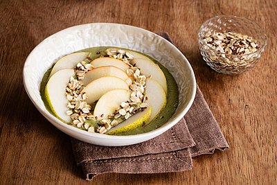 Bowl of sliced pears with oats and green smoothie - p300m2155934 by Eva Gruendemann
