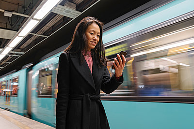 Young woman using smartphone in metro station - p300m2188158 by Hernandez and Sorokina