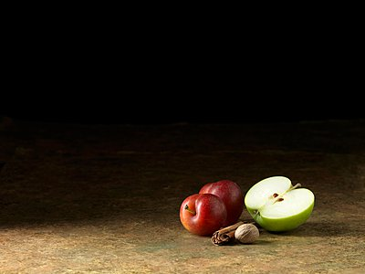 Apple, plums and nutmeg on surface - p429m1062869 by Diana Miller