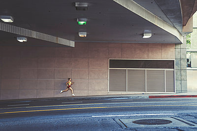 Portrait of young woman running along road - p924m1187570 by Kevin Kozicki