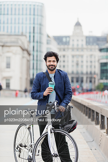 Portrait smiling businessman with coffee and bicycle on city bridge - p1023m2208415 by Paul Bradbury