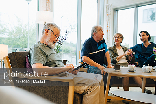 Senior man using smart phone while sitting with newspaper on armchair by friends and caretaker at elderly nursing home - p426m2149363 by Maskot