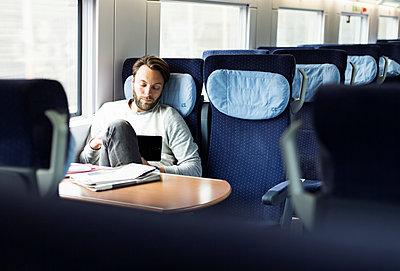 Mann im Zug mit Tablet - p1114m1159789 von Carina Wendland