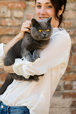 Young woman caressing a grey cat against brick wall - p1166m2096419 by Cavan Images