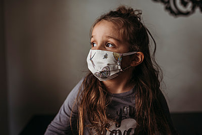 Close up of young girl with mask on looking out window - p1166m2207787 by Cavan Images