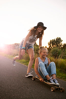 Zwei jugendliche Mädchen mit Skateboard - p1348m1496946 von HANDKE + NEU