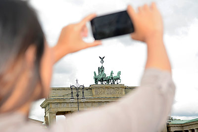 Germany, Berlin, young tourist photographing Brandenburger Tor with smartphone - p300m1081262f by Bernd Friedel