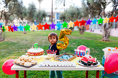 Little boy with golden balloon behind laid birthday table - p300m1189613 by Valentina Barreto