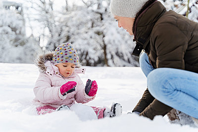 Happy mother playing with daughter in winter landscape - p300m2083328 by Daniel Ingold