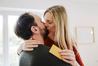 Happy couple standing at home, kissing, holding credit card - p300m2167266 by Kniel Synnatzschke