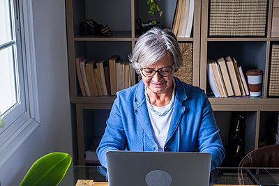 Smiling female entrepreneur working on laptop against bookshelf at home - p300m2276594 by Simona Pilolla