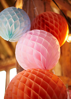 Paper baubles in pink  orange and blue  in late summer. - p349m2167853 by Sussie Bell