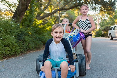 Children in swimsuits pushing cart on rural road - p555m1418843 by Marc Romanelli