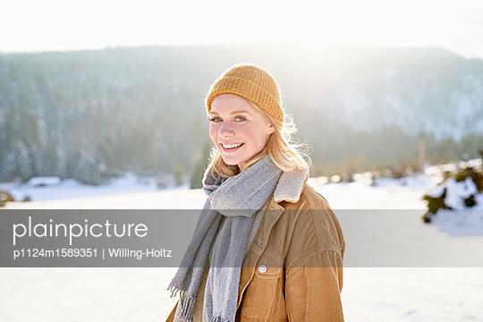 Junge Frau macht einen Winterspaziergang - p1124m1589351 von Willing-Holtz