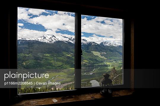 Snowy mountain ridge and green valley with curvy road located behind window of wooden cabin with retro lantern in highlands of British Columbia, Canada - p1166m2208545 by Cavan Images