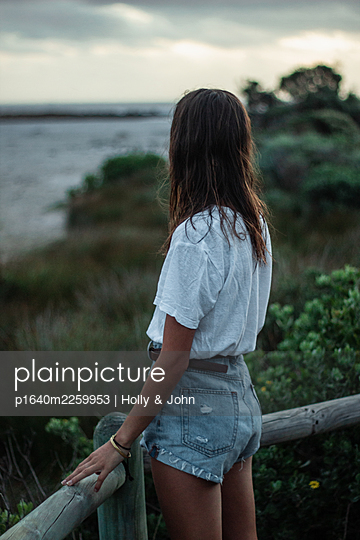 Young girl on wooden boardwalk - p1640m2259953 by Holly & John