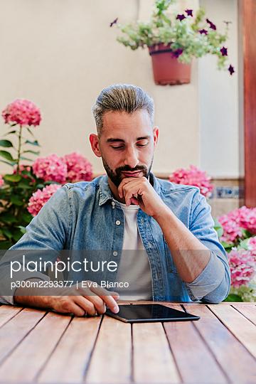Male freelance worker using digital tablet at desk - p300m2293377 by Eva Blanco