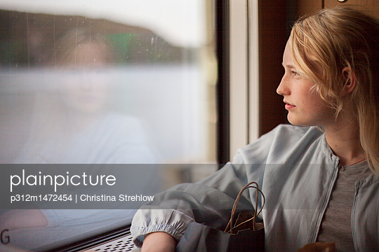 Teenage girl looking through window - p312m1472454 by Christina Strehlow