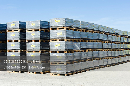 Cement stone in layers on pallets arranged in order against clear sky - p1025m780433f by Björn Andrén