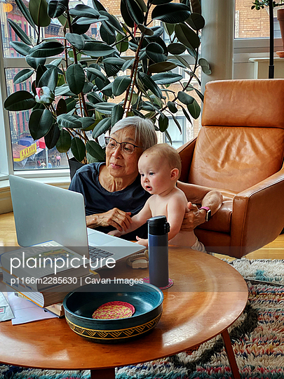 Asian Grandmother and Granddaughter using laptop together at home - p1166m2285630 by Cavan Images